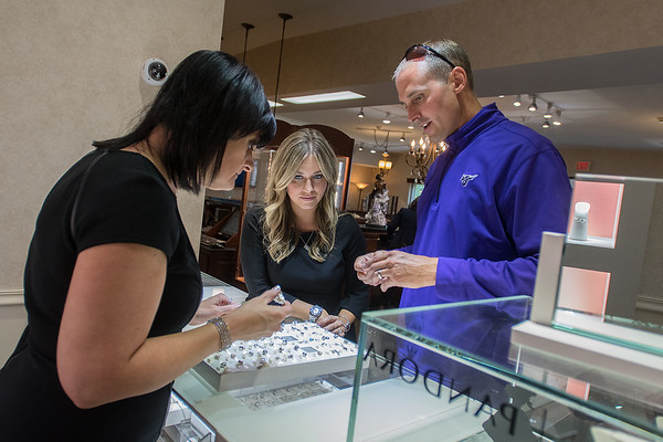 Jennifer Wendland (left) and Maria Person (center) help Todd Knott find a birthday present for his wife at Exclusively Diamonds. Exclusively Diamonds will be moving to the old Wells Federal Bank building in October. Photo by Jackson Forderer