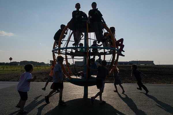 Children play on a large spinning globe at the newly opened Fallenstein Playground on Wednesday. The playground on the west end of Caswell Park is accessible to people of all ages and abilities. Photo by Jackson Forderer