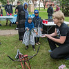 Hana Ahmed, 6, plays a game of ring toss with used bike parts with assistance from Jessica Myer (right) of Key City Bike during Night to Unite at Washington Park. Washington Park was one of forty locations that held Night to Unite community celebrations. Photo by Jackson Forderer
