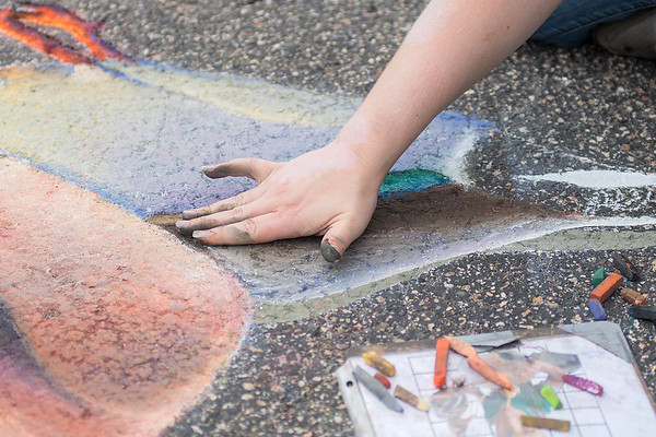 Jamie Rogers from Richland Center, Wisc. uses her hand to smudge chalk on a piece of 3D chalk at the first annual Chalkfest held on Saturday. Smudging the chalk is a practice commonly used to blend two colors or shade a piece of chalk work. Photo by Jackson Forderer
