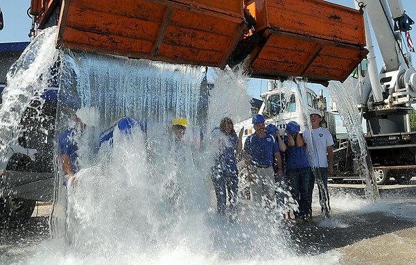 Employees of Kato Roofing Incorporated do their version of the popular ALS ice bucket challenge using a pair of the company's cranes Thursday afternoon. The company contribued $500 to the ALS Assocation, which has reportedly received more than $41 million in donations since the Internet sensation started. Photo by Pat Christman