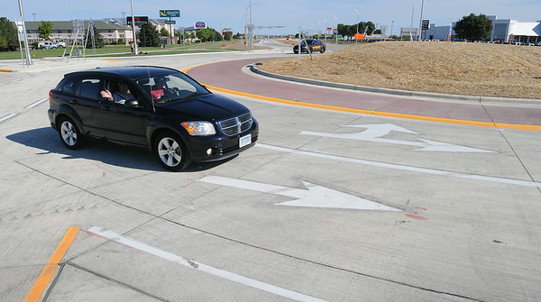 Vehicles travel through the recently completed roundabout at Madison Avenue and Highway 22 shortly after it officially was opened to traffic on Monday morning. John Cross photo.