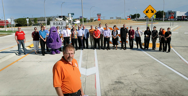 Business owners, governement officials and business representatives line up at the south entrance to a newly-completed roundabout behind Minnesota Department of Transportation District Engineer Greg Ous says a few words to a crowd gathered for its official opening on Monday. Photo by John Cross