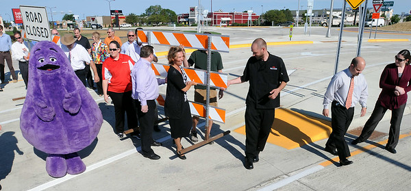 Business representatives and government officials remove barricades on Monday to officially open the recently completed Madison Avenue roundabout. Photo by John Cross
