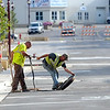 Workers replace a manhole cover along Front Street in downtown Mankato while getting ready to reopen the street Friday after a major reconstruction project. Photo by Pat Christman