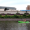 Denise Bicknase paddles past the Verizon Wireless Center and the Hilton Garden Inn while paddling toward Riverfront Park for Paddle Jam Saturday.