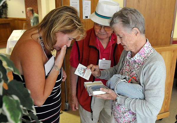Beverly Ebbecke and her husband George show Marti McClure Ryan a 350th anniversary Westwood commemorative of the Mayflower's sailing during a gathering of the Minnesota Society of Mayflower Decendents Saturday at Bethany Lutheran College.