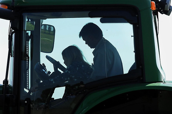John Cross<br /> Eric Schwarz takes Josie Carpenter for a tractor ride Monday during a Farm Camp Minnesota at Farmamerica. The camp was organized and sponsored by farmers and agri-businesses.