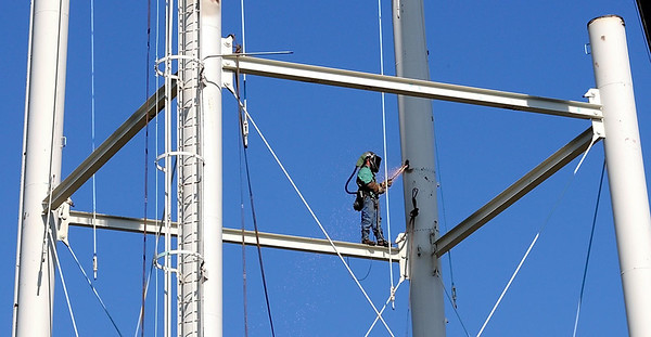 A worker cuts part of the frame of the old water tower Thursday.