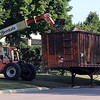 Workers load pieces of metal from the water tower into a trailer for recycling