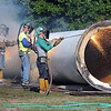 Workers from Iseler Demolition cut up a portion of the center pipe from the old North Mankato water tower Thursday.