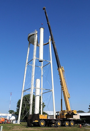 A crane lifts part of the center pipe from the old North Mankato water tower Thursday.