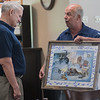 Madelia mayor Mike Grote presents Governor Mark Dayton with a signed piece of art work with Madelia land marks on it at the end of a round table discussion where many business owners thanked Dayton for the state's financial support to help rebuild their downtown. Photo by Jackson Forderer