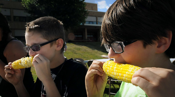 Brothers Ryan (front) and Jacob Wood work their way through ears of buttered sweet corn at the 56th Annual Y's Club Corn Roast at Mankato West High School on Monday. Funds raised through the event are used to fund community youth programs. Photo by John Cross