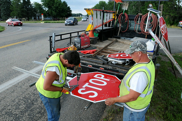 Crews assemble stop signs at the intersection of Nicollet County Road 20 and State Highway 22 on the north edge of St. Peter on Wednesday. Signs were erected to make the intersection, which was the scene of a fatal crash on Tuesday and a day after traffic from Highway 169 was detoured along that route, to a four-way-stop. Photo by John Cross