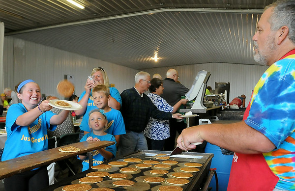 Pancake cook Gregg White sends airborne pancakes to waiting diners during Breakfast on the Farm at the Terry and Mary Guentzel farm between Mankato and Kasota on Saturday. The event was sponsored by the LeSueur and Blue Earth County Farm Bureaus. Photo by John Cross