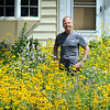 Pat Kunerth is surrounded chest-high with prairie plants and flowers two years after digging up the conventional lawn at his home at 119 Tile Street in West Mankato. Photo by John Cross