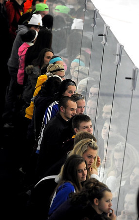 Fans of Mankato East/Loyola and Mankato West boys hockey fans' faces reflect in the glass along the rink while watching their teams play Thursday at All Seasons Arena.