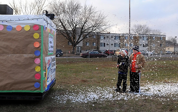 Cousins Carson and Jaeger Kennedy stand under a snow machine behind a fish house participating in Saturday's fish house parade in St. Peter.