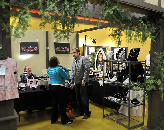Pat Christman<br /> Kathy Schnuck shows her husband Larry a necklace as she tries on jewelry at Wolfgang-Farnsworth Designs' booth at New Ulm's Christkindlmarkt.
