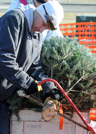 Pat Christman<br /> YMCA volunteer Eric Sletten cuts the trunk of a tree for a customer Saturday.