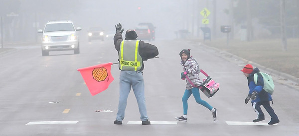 John Cross<br /> A crossing guard stops traffic along foggy Lee Boulevard for youngsters heading home from Hoover Elementary School  on Tuesday.