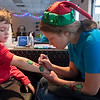 Westin Ruch (left), 7, gets holly painted on his arm by Aubrey Goettlicher of Making Faces Mankato at the Bells on Belgrade event held on Saturday in North Mankato. Photo by Jackson Forderer