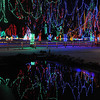 Holiday lights reflect in a pool near the barn in Sibley Park.