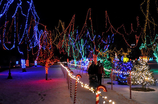 A family takes a stroll through the Kiwanis Holiday Lights display in Sibley Park.