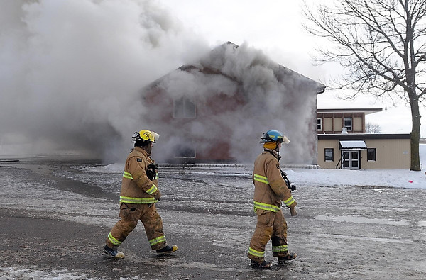 Pat Christman<br /> Firefighters walk past a smoking building during Saturday's practice burn.