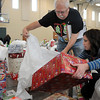 John Cross<br /> Rich Swing and his daughter, Laura Stueven, sort through some of the 3,200 gifts that were distributed to some 900 familes through the Holiday Sharing Tree on Wednesday.