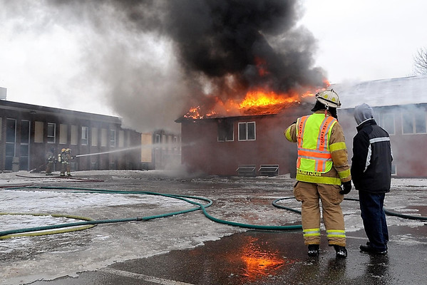 Pat Christman<br /> Deputy Director of Public Safety Jeff Bengtson talks with City Council president Chris Frederick during Saturday's practice burn as firefighters train their hoses on the back wall to keep it from collapsing into the neighboring building.