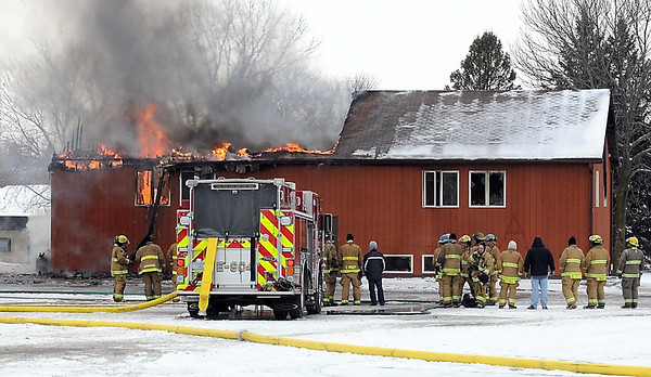 Pat Christman<br /> Firefighters watch as the wooden annex building burns Saturday.