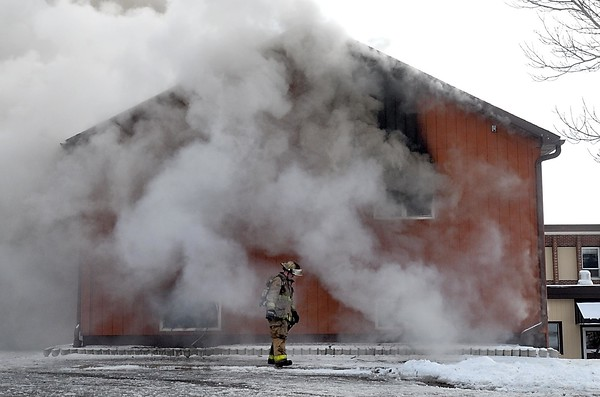 Pat Christman<br /> A firefighter checks on the progress of a practice burn of the wooden annex to the former MnDOT regional headquarters building.