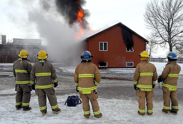 Pat Christman<br /> Firefighters watch as a wooden annex to the former Minnesota Department of Transportation regional headquarters building burns during a practice burn Saturday.