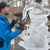 "Adam Scholljegerdes works on an ice sculpture of the Grinch on Saturday at Kiwanis Holiday Lights in Sibley Park. Fellow ice sculptor Deneena Hughes said, ""We all want to see each other succeed, everybody wants a good sculpture."" When completed, the four different ice sculptures will be lit for those visiting the festival. Photo by Jackson Forderer"