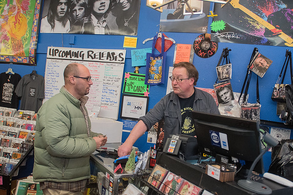 "Tune Town owner Carl Nordmeier (right) helps Shawn Lochner check out items at the store on Wednesday. ""I should be Christmas shopping but I end up buying stuff for myself,"" Lochner said. Photo by Jackson Forderer"