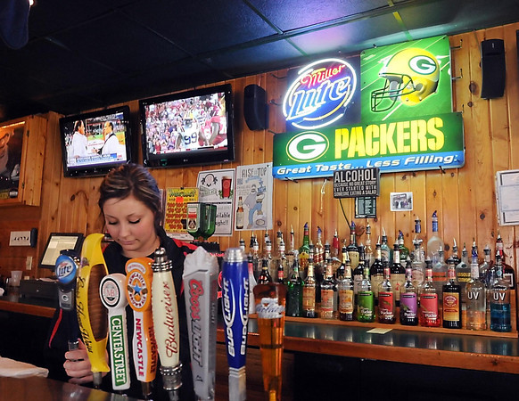 Courtney Werpy taps a beer for a customer at Spinner's Bar.