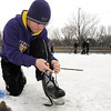 Isaiah Lacina laces up his skates as friends and family get warmed up for a game of hockey on the Stoltzman Road hockey rink Thursday afternoon, an activity that was nearly impossible last year due to the warm winter.
