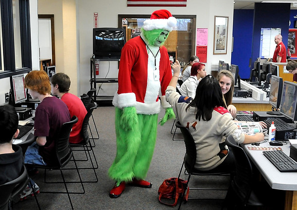 Mankato West media specialist Paul Christianson makes a convincing Grinch as he chats with students Friday in the high school's media center. Christianson said he's been dressing as the Grinch since the Jim Carrey version of the Christmas classic came out in 2000.