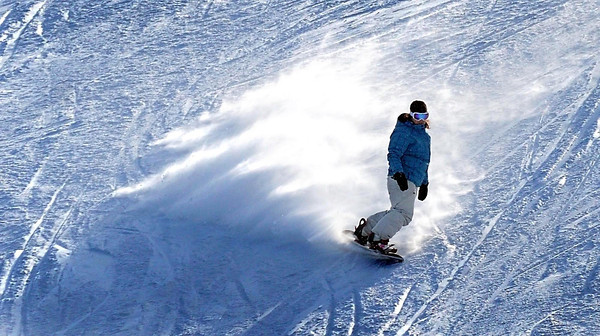 A snowboarder's edge sends fresh powder into the air during a run Friday at Mount Kato. General Manager Jeff Putrah said fresh snow always brings out skiers and snowboarders.