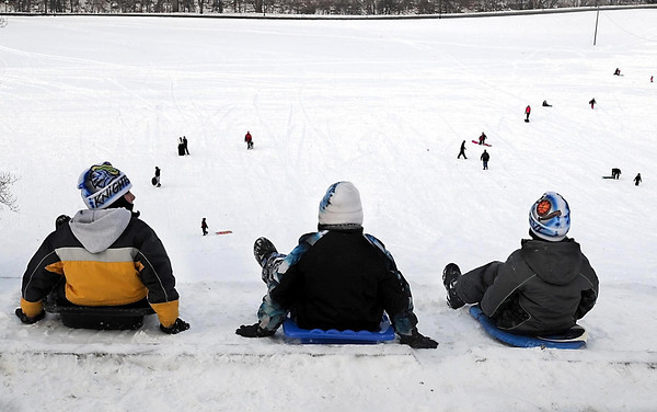 A trio of boys get ready to take a run down the Sibley Park sledding hill Friday afternoon.