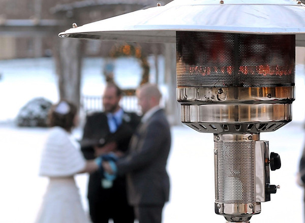 A patio heater struggles to keep guests warm as Katlyn McKenzie and Robert Grover exchange vows Friday.