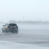 A car plunges into wind driven snow along County Road 90 this week.