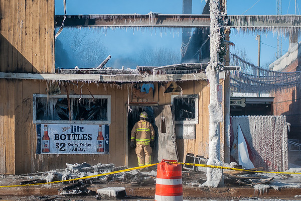 Janesville Assistant Fire Chief Chad Schroeder looks at the inside of the Dog House Bar & Grill on Wednesday morning after a fire destroyed the property. Photo by Jackson Forderer