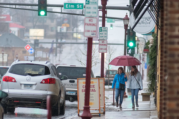 Megan (right) and Kari Lund shield themselves from the rain while walking through Old Town in Mankato on Thursday afternoon. Other parts of Minnesota weren't as lucky to get rain, receiving up to 10 inches of snow. Photo by Jackson Forderer