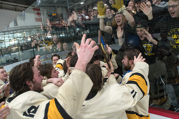 The Mankato East/Loyola boys hockey team brings the Section 1A championship trophy to the East student section after defeating Rochester Lourdes 6-1 on Wednesday. Photo by Jackson Forderer