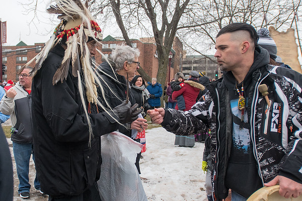 Eric Bates (right), a Cherokee Tsalagi, gives an eagle feather to elder Chief Arvol Looking Horse at the end of the Dakota 38+2 Memorial on Wednesday. Photo by Jackson Forderer