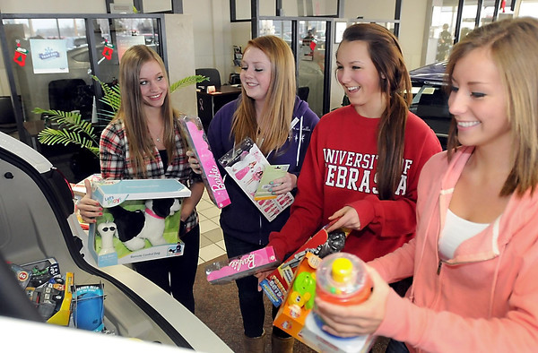 From left, Mankato East Dance Company members Bethany Mueller, Hannah Rosenwinkel, Nicole Piowlski and Kristina Case load toys being donated to Toys For Tots Friday into the back of a SUV at Mankato Ford. The company, which also received a $300 donation from Mankato Ford, collected more than 30 toys to be donated to Toys For Tots.