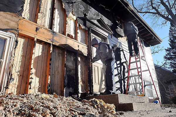 John Cross<br /> Workers from Service Master work on the burned out facade of a house at 143 Swiss Street.